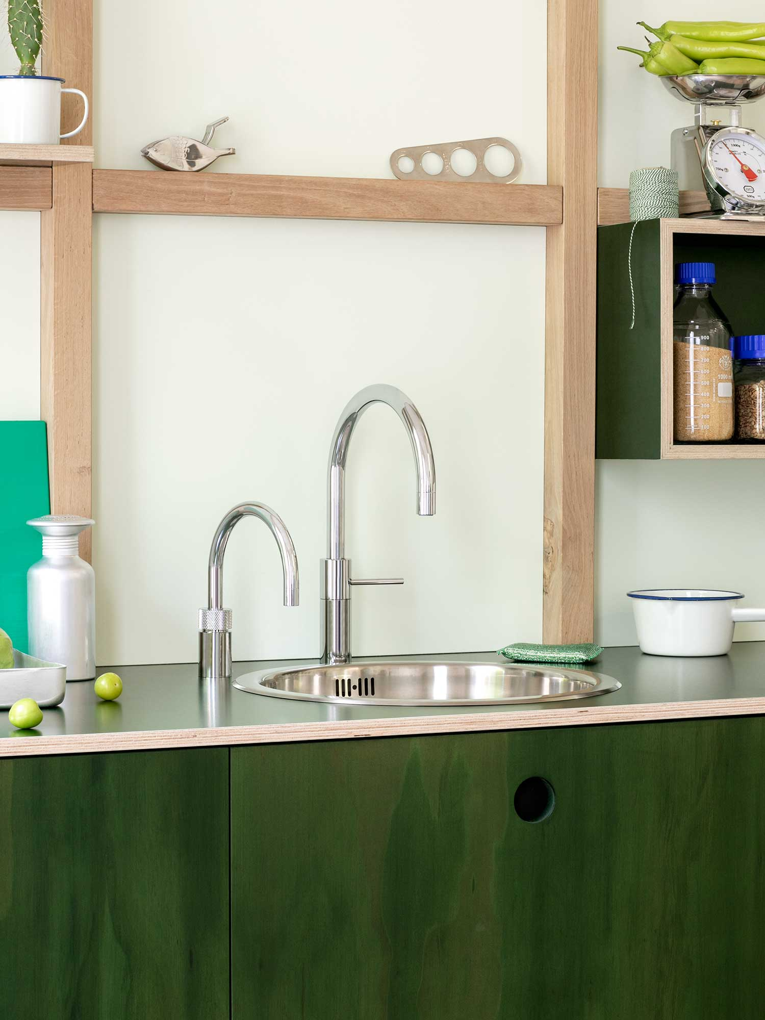 Quooker tap with nordic round design and sink on green counter