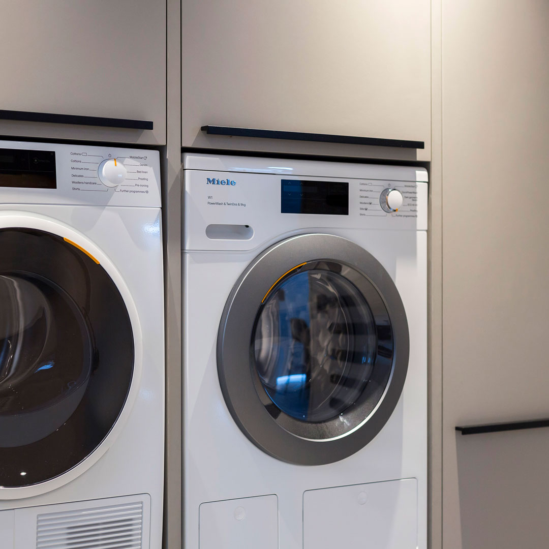The utility provides functional space for laundry, with elevated Miele appliances and plenty of dedicated storage. The colours and worktop are continued from the kitchen, creating a stylish yet practical space.